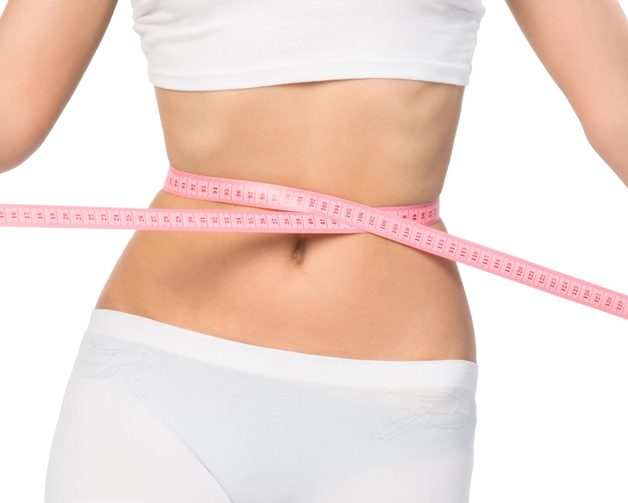 Women measuring her waistline with tape measure.